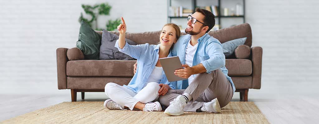 Junges Paar, Couch, Tablet, Frau zeigt in die Luft