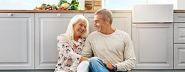 Älteres, glückliches Paar sitzen in der Küche