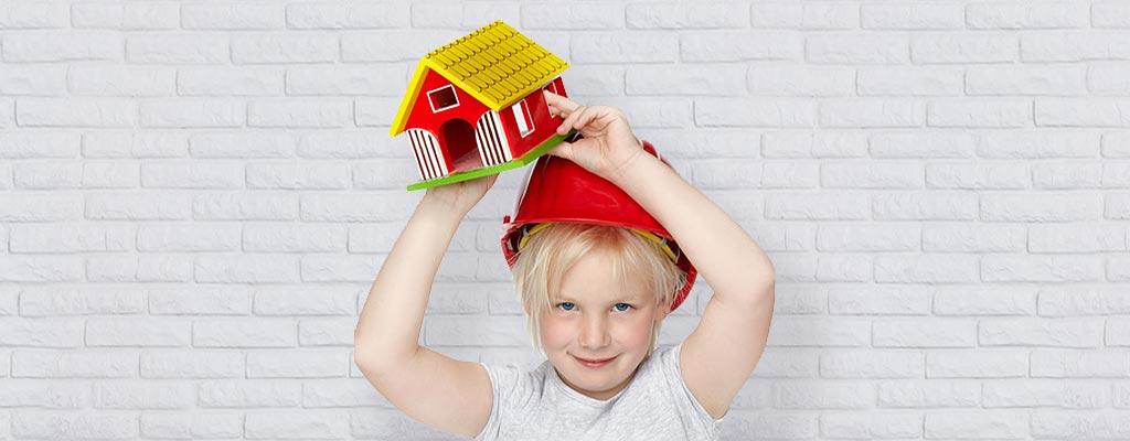 Kind mit Bauhelm, Spielzeughaus